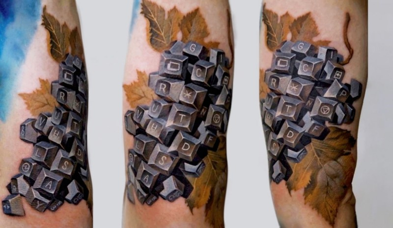 Funny looking colored arm tattoo of plant made from keyboard keys