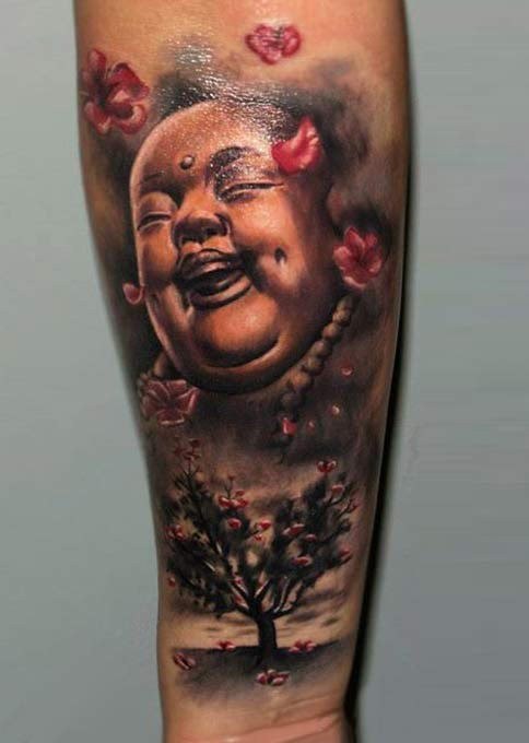 Funny looking colored forearm tattoo of Buddha statue and blooming tree