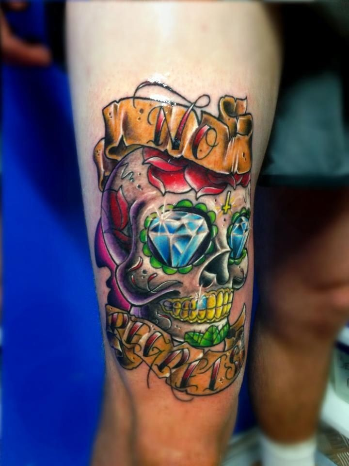 Funny looking colored thigh tattoo of human skull with diamonds and lettering