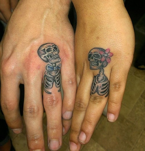 Funny man and woman skeleton romantic couple colored tattoos on ring fingers