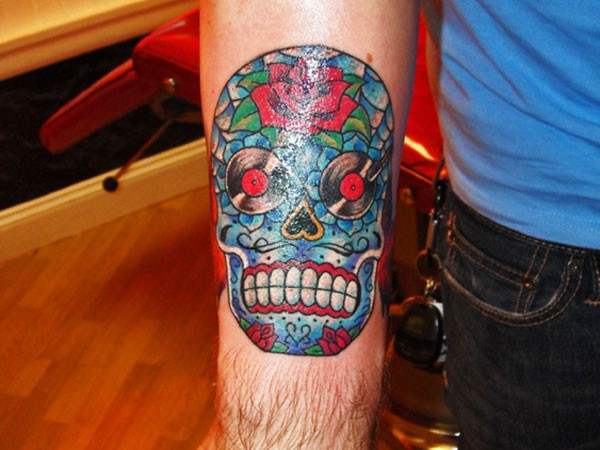 Funny Mexican style multicolored skull tattoo on forearm stylized with red roses