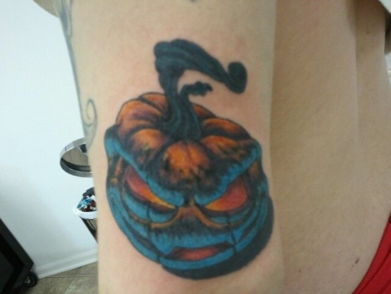 Funny monster like colored little pumpkin tattoo on arm