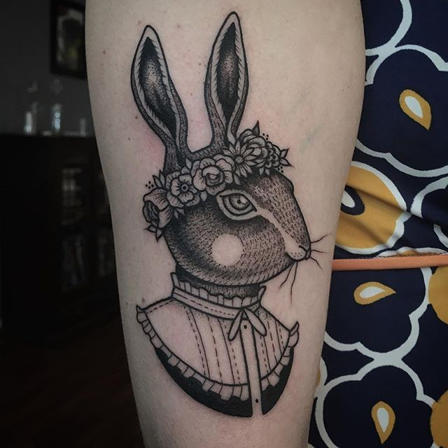 Funny old vintage like funny human rabbit tattoo on forearm stylized with flowers