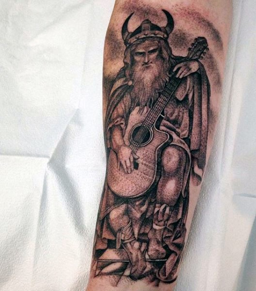 Funny painted black and white viking warrior playing the guitar tattoo on arm
