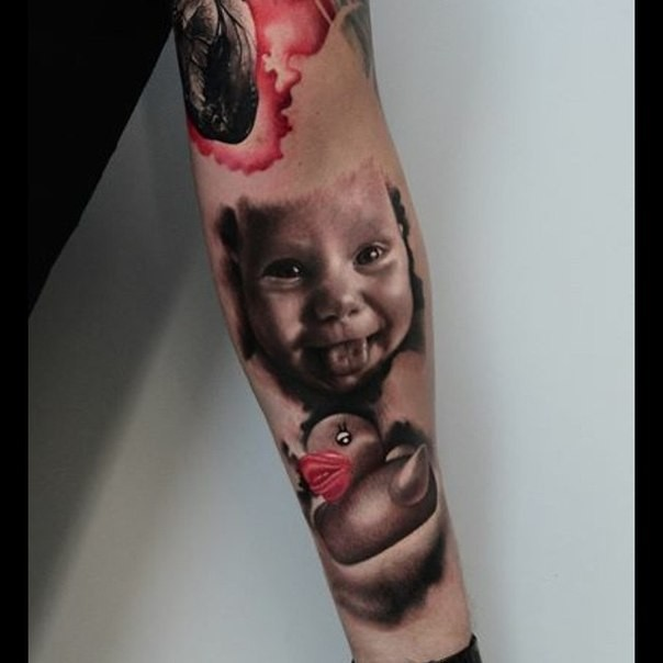 Funny portrait style colored forearm tattoo of smiling boy with duck