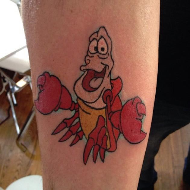 Funny Sebastian naturally colored Ariel cartoon hero tattoo on forearm