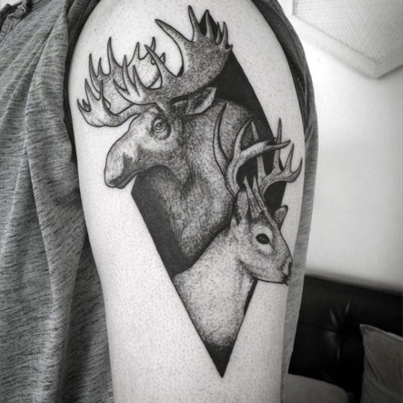 Geometrical shaped black ink tattoo on shoulder stylized with elk and deer