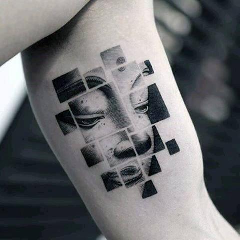 Tatuaggio bicipite in inchiostro nero di stile geometrico del ritratto di Buddha