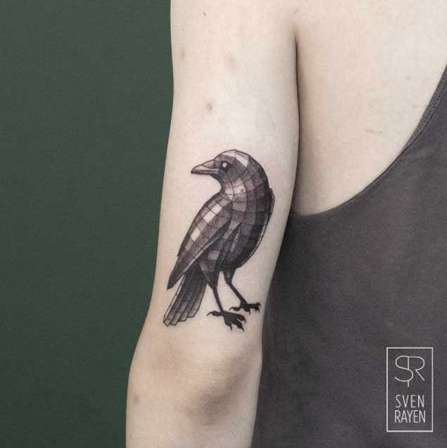 Geometrical style colored arm tattoo of small bird