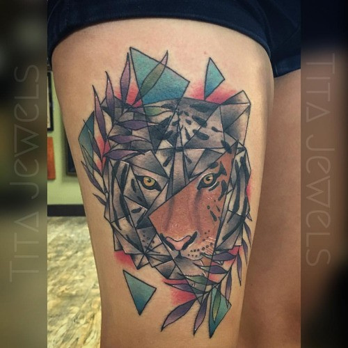 Geometrical style colored thigh tattoo of tiger head with leaves