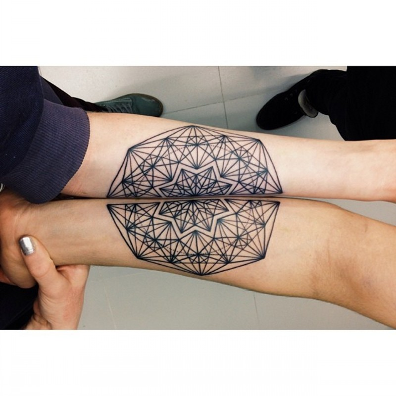 Geometrical style little black ink ornament tattoo on arm