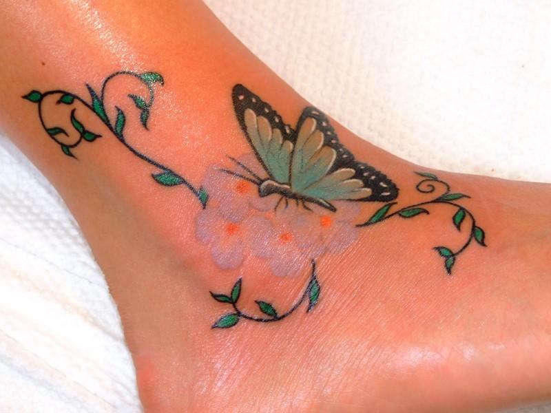 tatuaggio creativo farfalla e fiori  su caviglia di ragazza