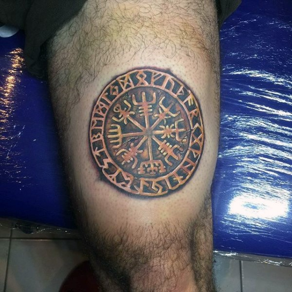 Golden like colored thigh tattoo of ancient emblem