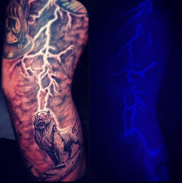 Gorgeous black and white lion with lightning glowing ink painted tattoo on sleeve