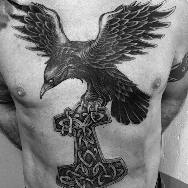 Gorgeous black ink chest and belly tattoo of big crow with Celtic cross