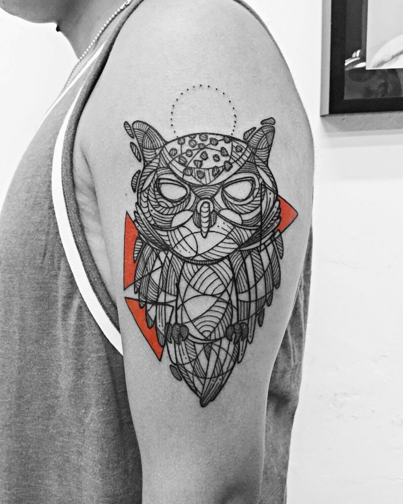 Gorgeous black ink owl tattoo on shoulder stylized with ornaments and colored triangles