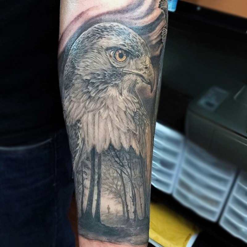 Gorgeous colored very detailed eagle head tattoo on forearm with dark forest