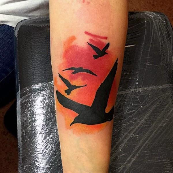 bel disegno colorato cielo uccelli bolanti tatuaggio su braccio