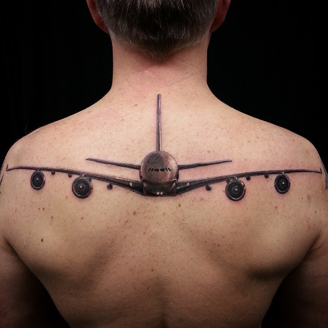 Gorgeous lifelike colored upper back tattoo of big plane