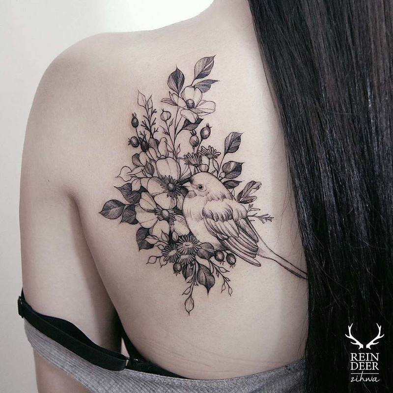 Gorgeous looking black outline style painted by Zihwa scapular tattoo of bird with flowers