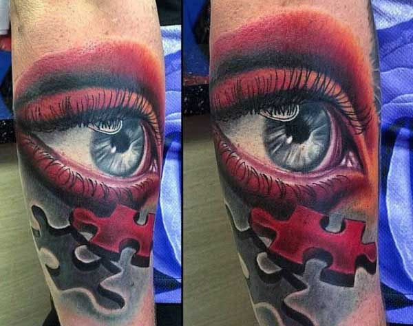 Gorgeous looking colored forearm tattoo of woman eye with puzzle piece