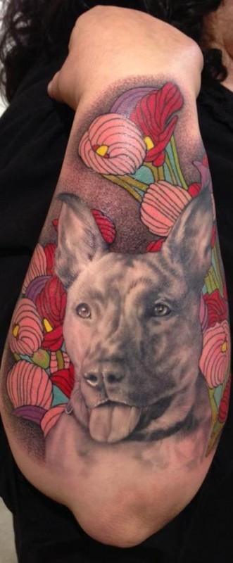 Gorgeous real photo like colored dog portrait tattoo on forearm stylized with flowers