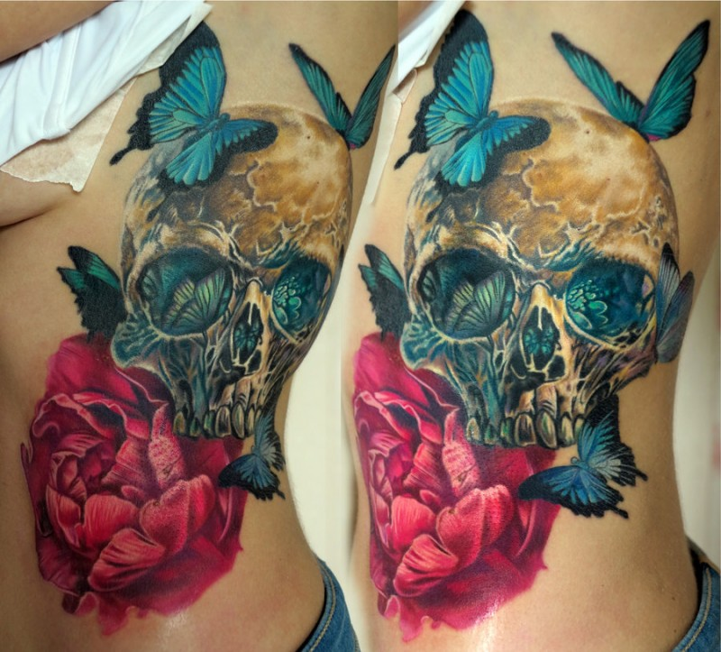 Gorgeous very detailed and colored human skull tattoo on side with flower and butterflies