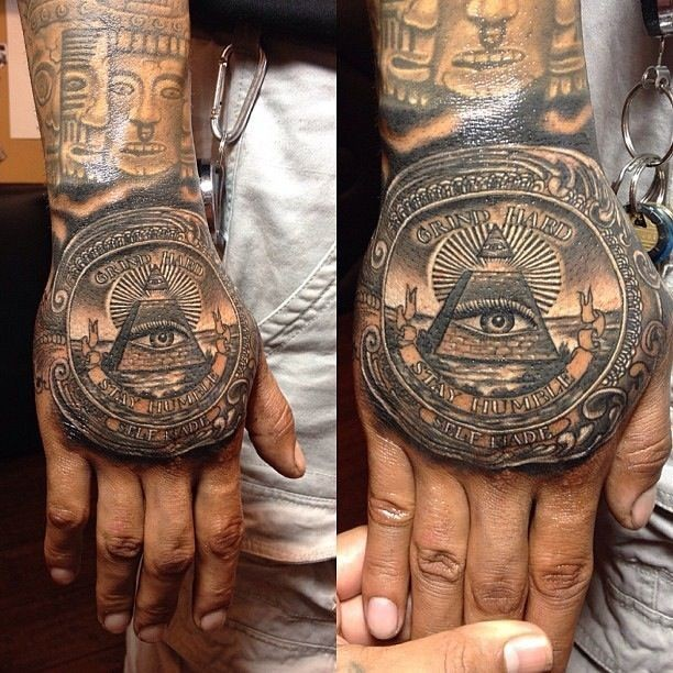 Gorgeous very detailed colored mystical pyramid tattoo on hand stylized with lettering