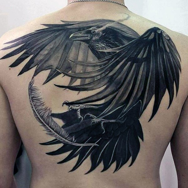 Gorgeous very detailed massive black ink crow with feather tattoo on upper back