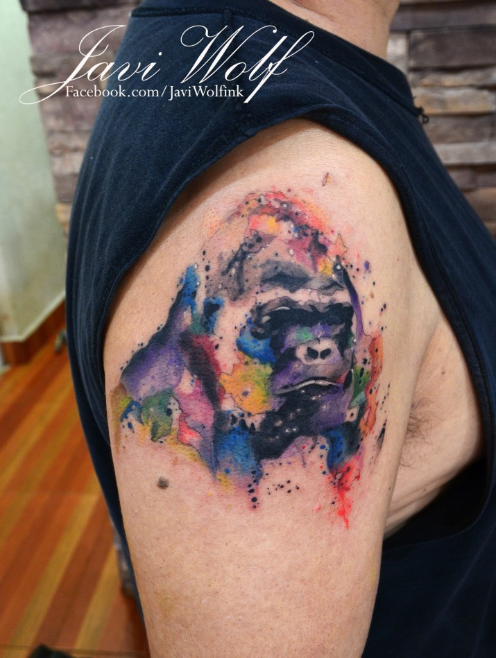 Gorilla&quots portrait with multicolored paint drips tattoo on upper arm in watercolor style by Javi Wolf