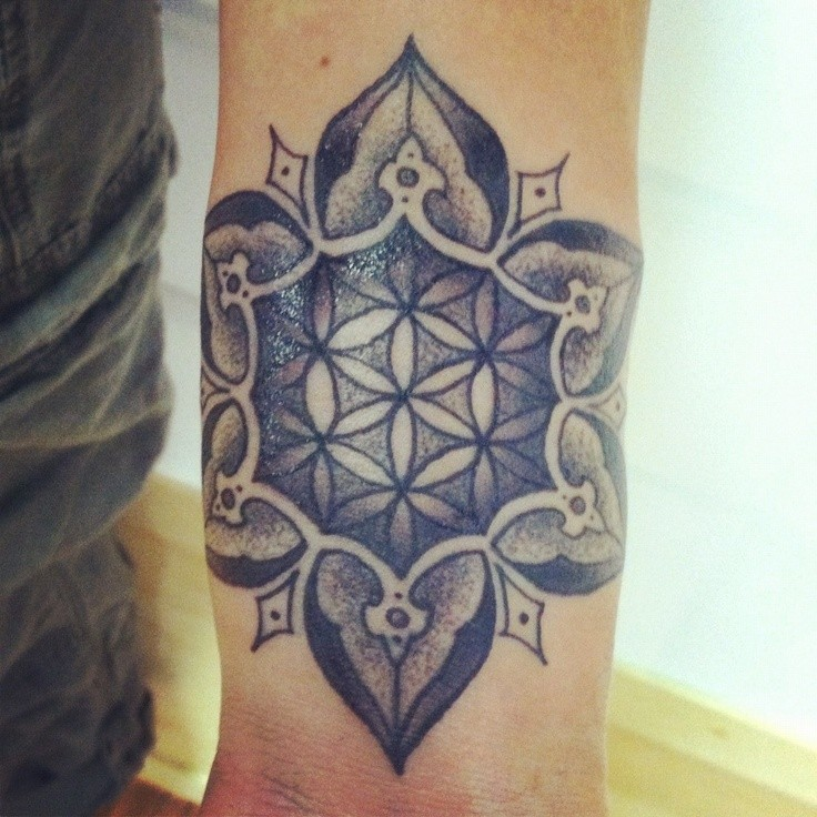 Gray-ink flower of life in mandala tattoo on arm