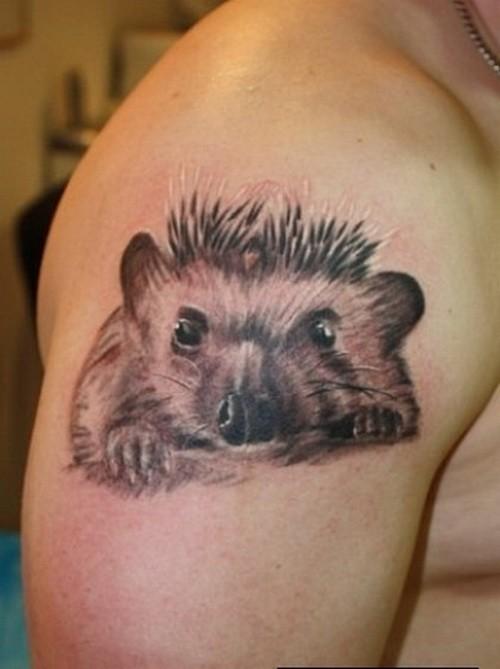 Gray ink hedgehog head tattoo on upper arm