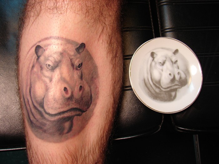 Gray-ink hippo tattoo on leg by photo