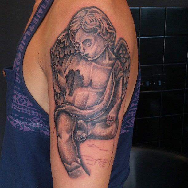 Gray ink little sitting cherub tattoo on shoulder