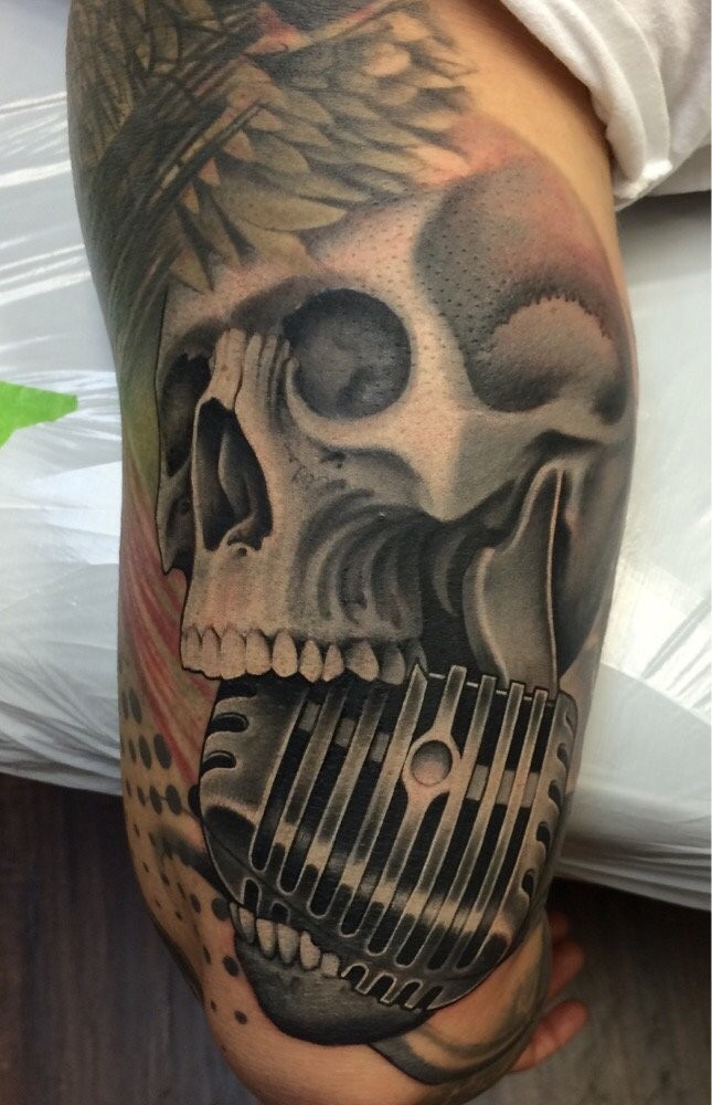 Gray washed colored arm tattoo of human skull with microphone