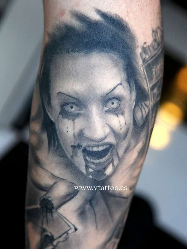 Gray washed horror style forearm tattoo of bloody woman portrait