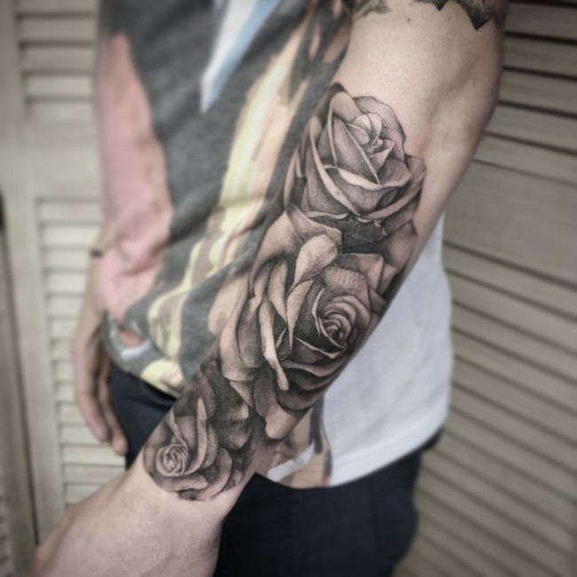 Gray washed style big realistic looking roses tattoo on forearm