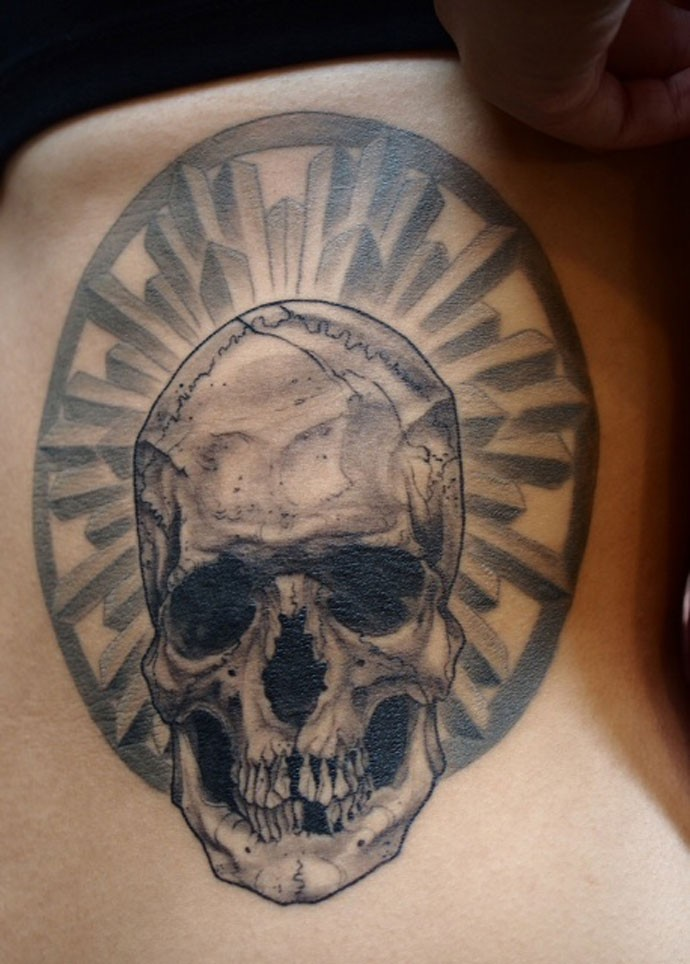 Gray washed style black ink side tattoo fo human skull with ornament