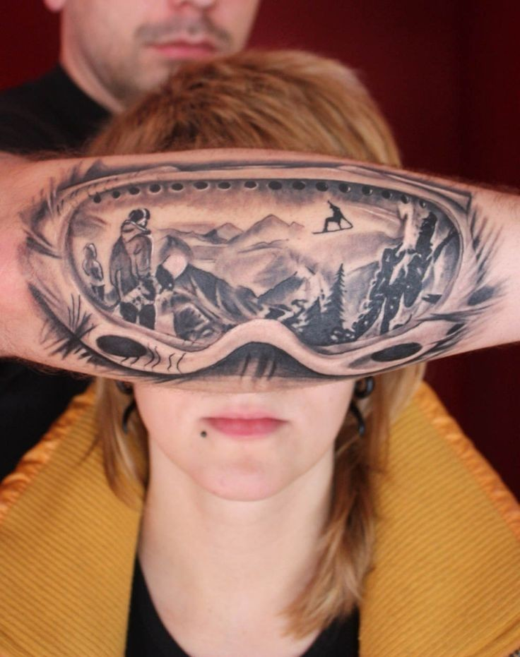 Gray washed style colored arm tattoo of snowboarders mask