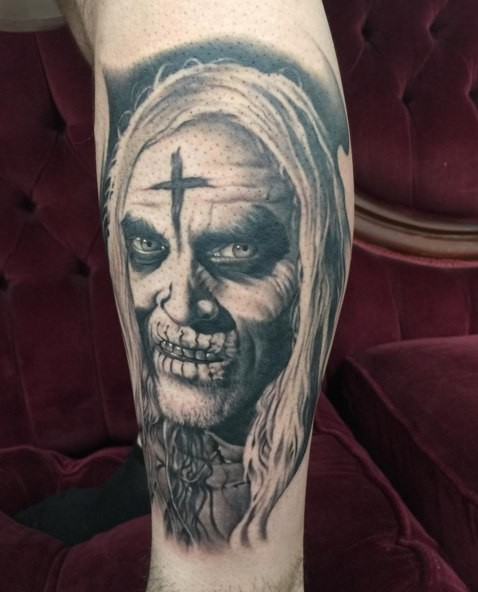 Gray washed style colored leg tattoo of creepy human face with cross