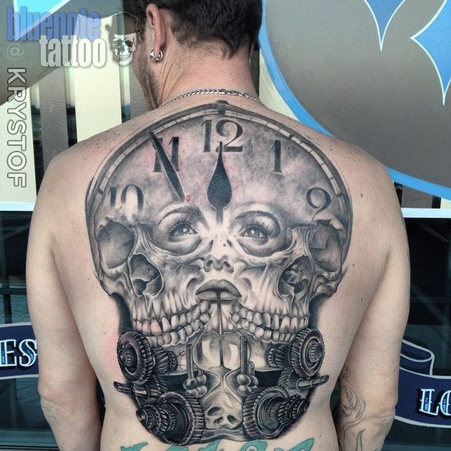 Gray washed style colored whole back tattoo of clock with human skulls and woman faces