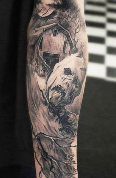 Gray washed style creepy looking monster scarecrow tattoo on forearm with old farm