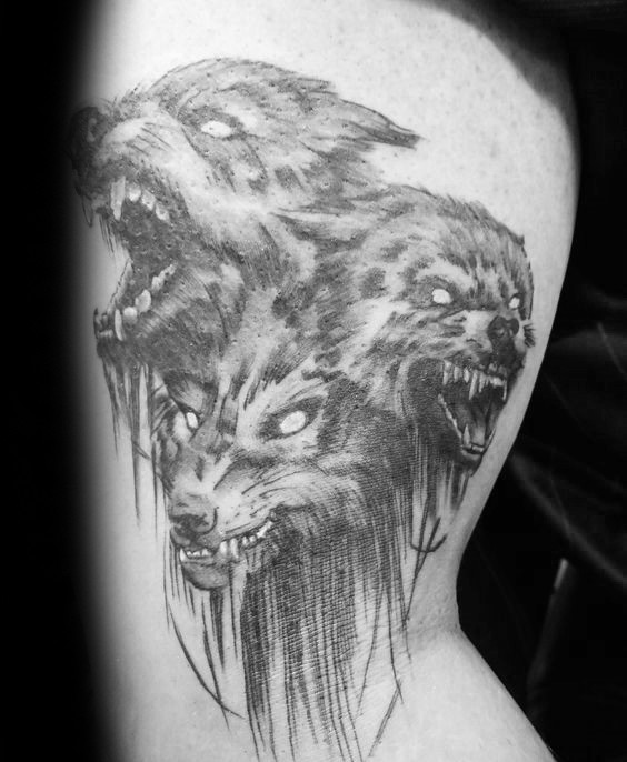 Gray washed style detailed biceps tattoo of Cerberus dog