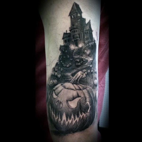 Gray washed style detailed creepy house with pumpkins field tattoo on forearm