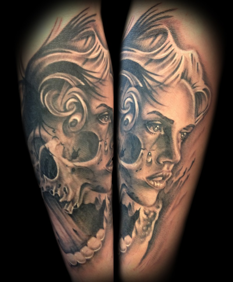 Gray washed style detailed forearm tattoo of crying woman stylized with skull