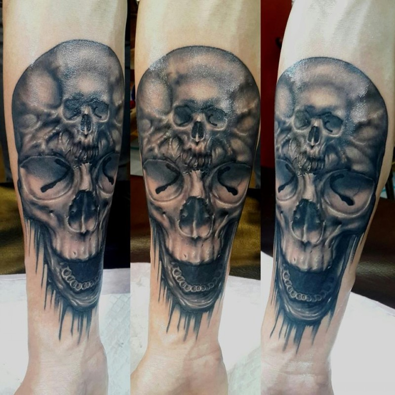 Gray washed style detailed forearm tattoo of human skull stylized with smaller skull