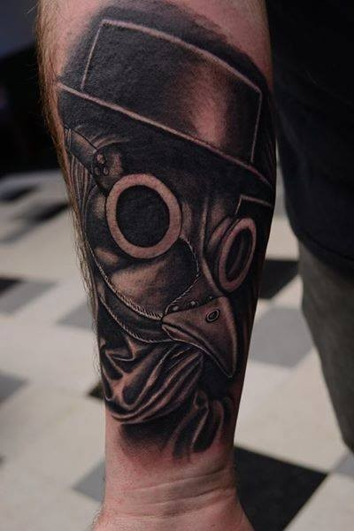 Gray washed style detailed forearm tattoo of plague doctors mask