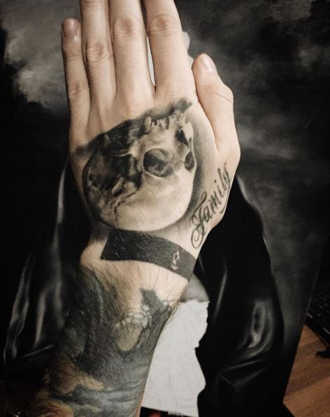Gray washed style detailed hand tattoo of small skull with lettering