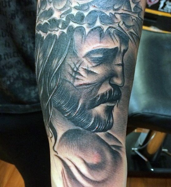 Gray washed style dramatic looking arm tattoo of sad Jesus portrait