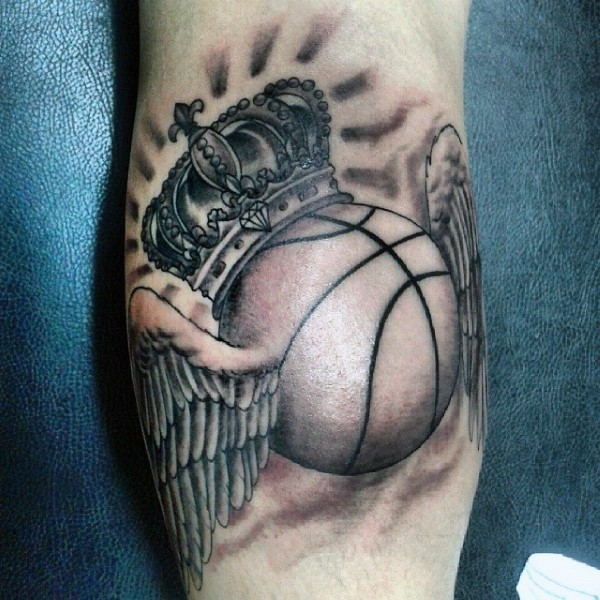 Gray washed style leg tattoo of basketball with wings and crown